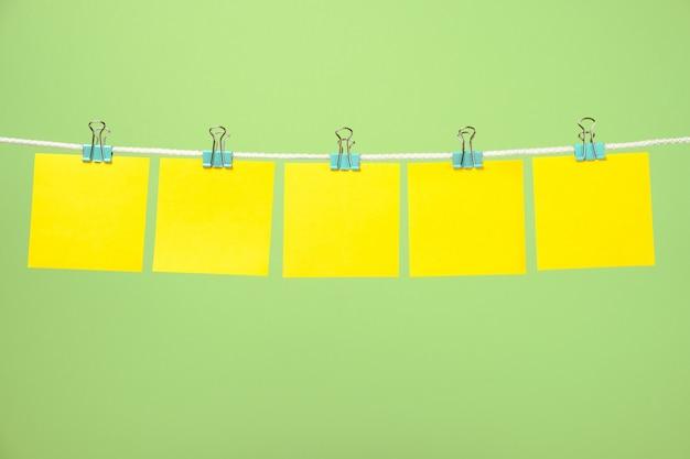 Hojas de papel amarillo en blanco en la cuerda