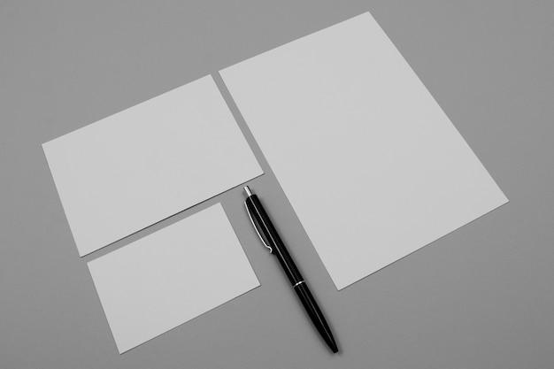 Hojas de papel de ángulo alto y bolígrafo negro