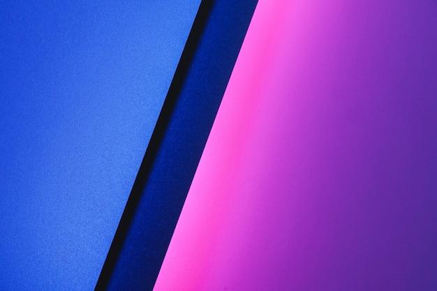 Hojas de papel en blanco enrolladas en una iluminación de neón púrpura