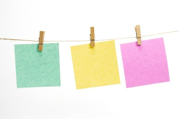 Hojas de papel de color vacías para notas, marcos que cuelgan de una cuerda con pinzas para la ropa y aislados en blanco.