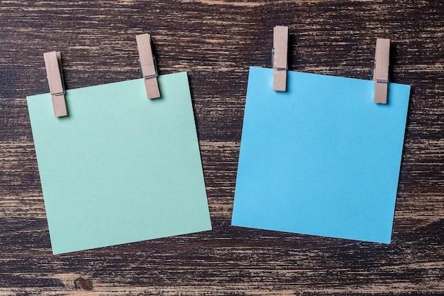 Hojas de papel de colores vacías para notas con pinzas para la ropa sobre fondo de madera. tarjetas en blanco en plantilla de maqueta. pinzas de madera con hojas de papel. concepto de negocio, espacio de copia