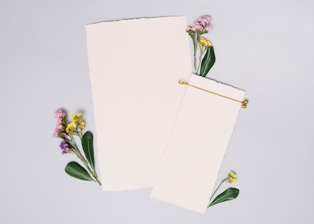 Hojas de papel con pequeñas ramas en mesa blanca.