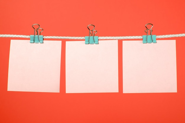 Hojas de papel rosa en blanco colgando de cuerdas