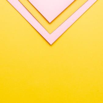 Hojas de papel triangular rosa con espacio de copia