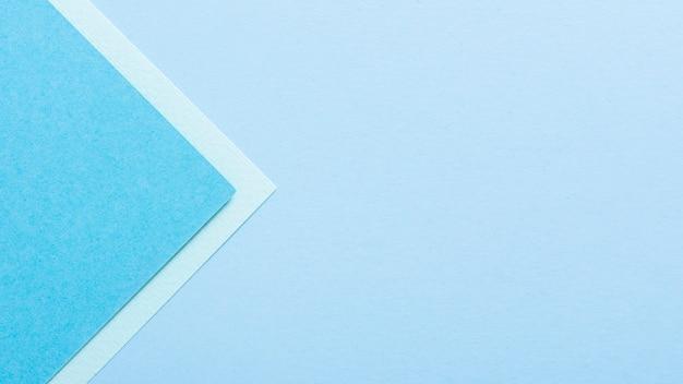 Hojas de papel triangular en tonos azules con espacio de copia
