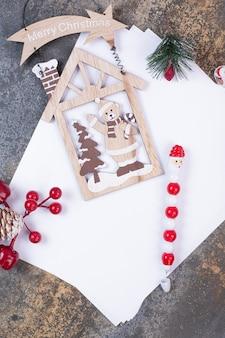 Hojas de papel vacías con adornos navideños en espacio de mármol.