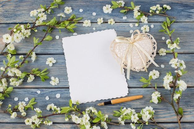 Hojas de papel vacías, corazón de encaje, pluma estilográfica y ramas de cerezo