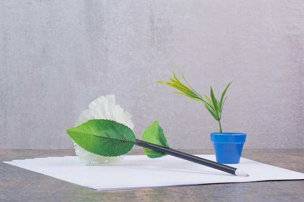 Hojas de papel vacías con lápiz sobre la superficie de mármol