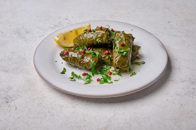 Hojas de parra rellenas con carne de arroz, perejil, pimienta y limón en la vista superior de la placa blanca dolma light