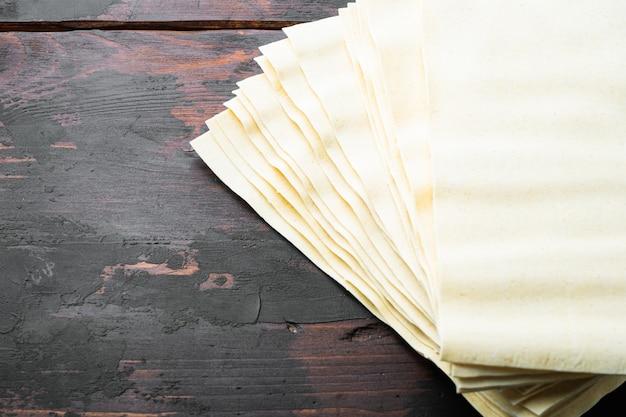 Hojas de pasta de lasaña sin cocer secas, sobre la vieja mesa de madera oscura.
