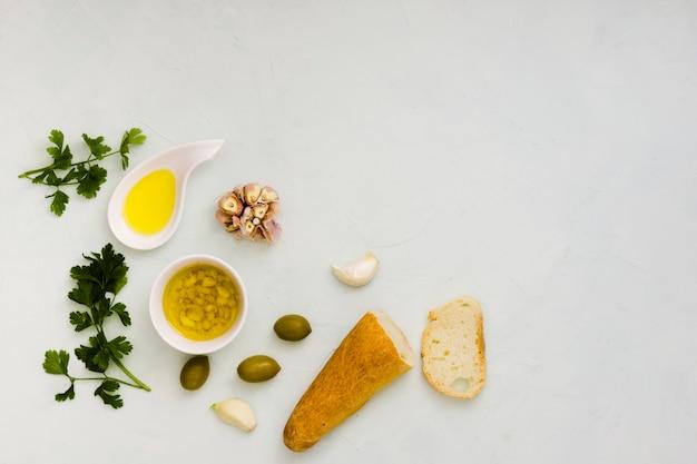 Hojas de perejil; aceite de oliva; ajo y pan sobre fondo blanco con textura