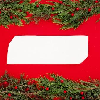 Hojas de pino de navidad en rojo con una tarjeta de felicitación en blanco