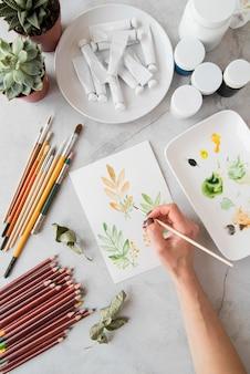 Hojas de pintura de mano de primer plano