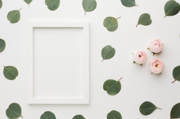 Hojas planas y rosas con marco de espacio de copia
