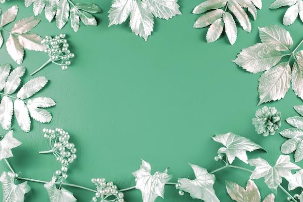 Hojas de plata sobre fondo verde menta, espacio de copia, vista superior