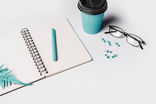 Hojas y pluma artificiales del helecho en el cuaderno espiral en blanco blanco con la taza de café; anteojos y alfiler