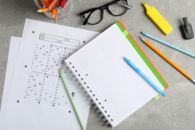 Hojas de prueba, cuaderno, gafas y papelería sobre superficie gris, vista superior