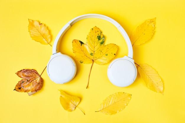 Hojas realistas y auriculares blancos sobre fondo amarillo lista de reproducción de otoño o podcast