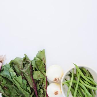 Hojas de remolacha; cebollas y judías verdes en el recipiente sobre fondo blanco
