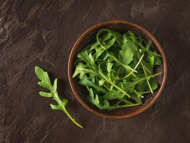 Hojas de rúcula fresca en un cuenco de arcilla sobre una mesa de piedra. dieta saludable a base de plantas. cocina vegetariana.