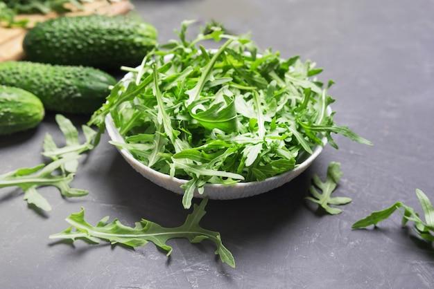 Hojas de rúcula fresca en un tazón sobre la mesa oscura.concepto de comida vegetariana fresca, primer plano