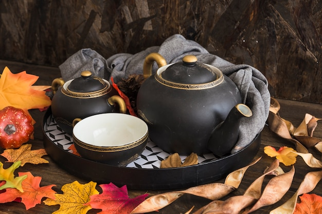 Hojas secas alrededor de juego de té