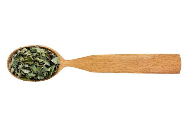 Hojas secas de fragaria vesca en una cuchara de madera sobre un fondo blanco. fitoterapia y prevención de enfermedades.