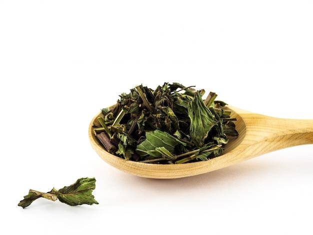 Las hojas secas de menta se encuentran en una cuchara de madera sobre un blanco