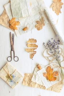 Hojas secas de otoño flatlay sobre fondo blanco de madera con papel, lavanda tijeras rústicas vintage