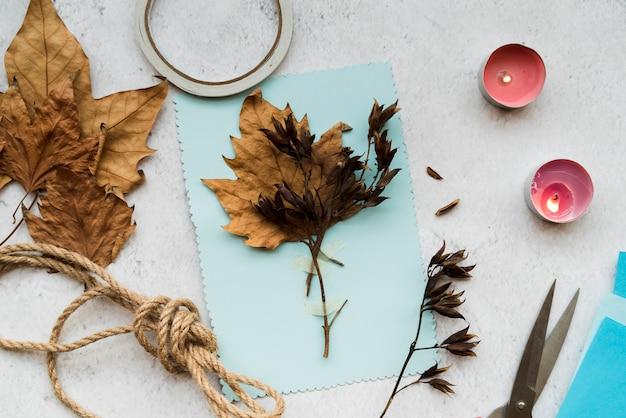 Hojas secas de otoño sobre papel azul con hilo y velas encendidas sobre el fondo blanco