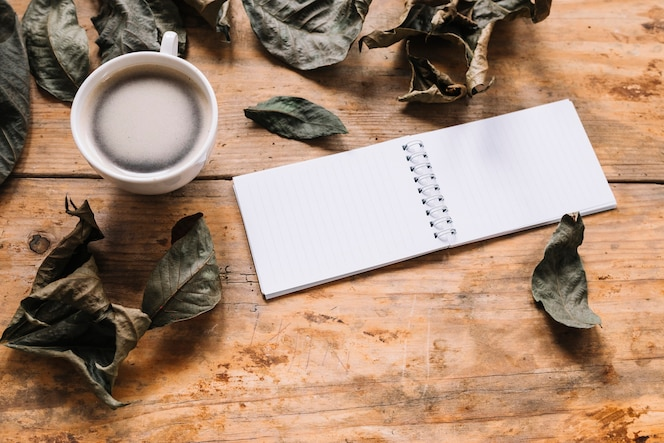 Hojas secas, taza de café y cuaderno sobre fondo de madera