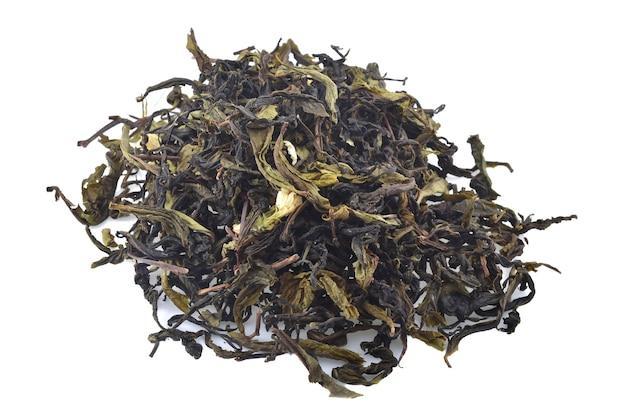Hojas secas de té verde aislado sobre fondo blanco.