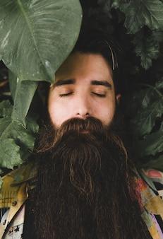 Hojas sobre barbudo joven con ojo cerrado.