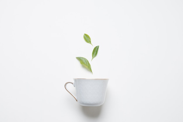 Hojas de té de limón sobre la taza de porcelana sobre fondo blanco