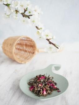 Hojas de té secas para infusión con pétalos de flores rosas secas en un plato pequeño en forma de hoja.