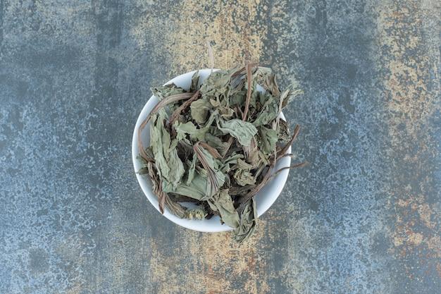 Hojas de té secas naturales en un tazón blanco.