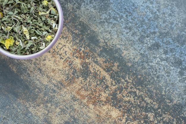 Hojas de té secas orgánicas en un tazón blanco.