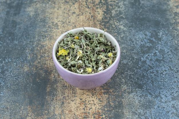 Hojas de té secas orgánicas en un tazón púrpura.