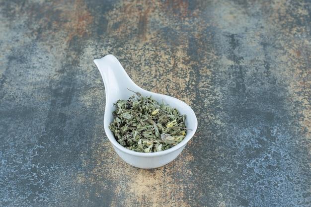 Hojas de té secas en un tazón blanco.