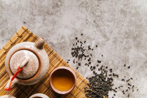Hojas de té secas con tetera y tazón sobre mantel sobre el fondo de hormigón