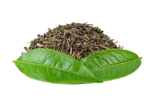 Hojas de té verde con hojas de té secas aisladas sobre fondo blanco.