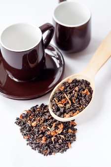 Hojas de té verde secas con pétalos de flores en una cuchara de madera y una taza con platillo