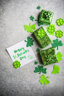 Hojas de trébol decorativo, caja de regalos verde, monedas sobre fondo de piedra, plano laical. celebración del día de san patricio. tarjeta feliz día de san patricio