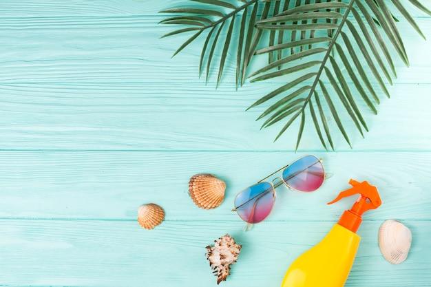 Hojas tropicales con accesorios de playa en composición.