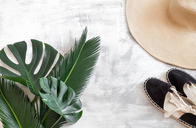 Hojas tropicales en blanco con accesorios de verano.