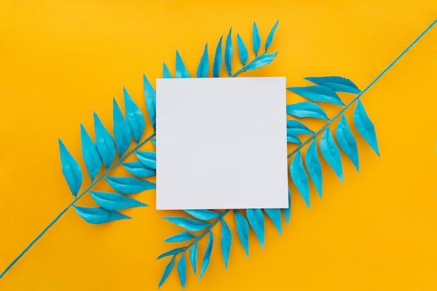 Hojas tropicales exóticas y papel en blanco sobre amarillo