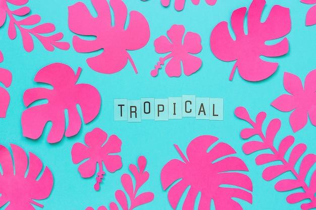 Hojas tropicales de moda rosa de papel y texto inscripción tropical sobre fondo azul