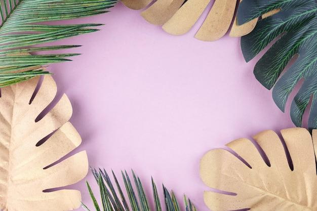 Hojas tropicales de oro, verde sobre fondo rosa. palmera tropical. fondo moderno abstracto. papel pintado de playa.