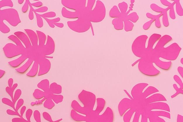 Hojas tropicales de papel con espacio de copia para su diseño o texto de letras sobre fondo rosa.