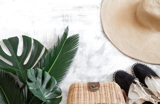 Hojas tropicales sobre un fondo blanco con accesorios de verano concepto de vacaciones de verano y recreación. banner de cartel, plantilla de tarjeta postal.